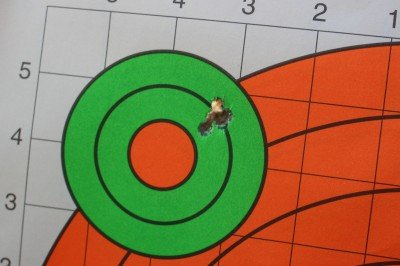 vHow's this for a five round group? While I'd hoped to have that ragged hole right in the orange dot, this type of reliability is admirable from a stock AR. There are a lot of ARs, many of which are much more expensive, that won't shoot half this well.