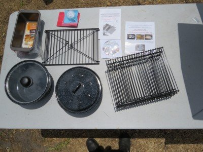 The$399  Sun Oven kit comes with a swinging leveling rack, three stackable drying racks, two pots, two baking pans and directions for everything.  The $349 doesn't have the pans.