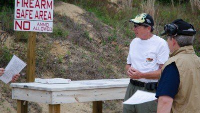 Local Match Director, Chuck Limpert gives new shooters a safety and rules orientation. Note that there is a designated area for safe firearm handling.