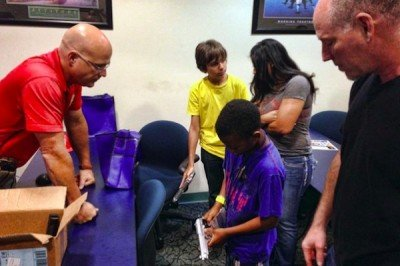 Using replica firearms, the deputy trainer shows children how to safely hold a firearm. (Photo: Sun-Sentinel)