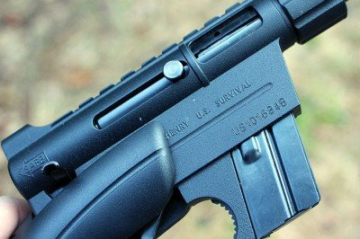 The charging handle, the little nub pictured here, slides back into the bolt, which keeps it out of the way.
