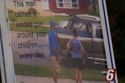 """Here's a image of the sign, which has a caption, """"This man carries a loaded gun around your children every day."""" (Photo KAAL-TV)"""