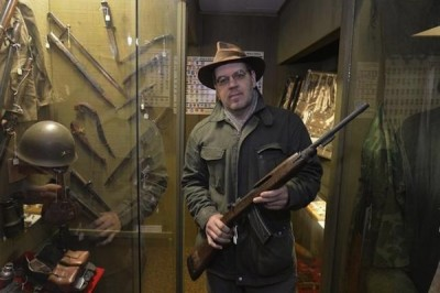 Lynden Museum Director Troy Luginbill holds a Korean War-era M1 carbine Tuesday, Nov. 18, 2014, on loan to the museum. The museum has decided to return the M1 carbine and 10 other loaned weapons to their owners to comply with Initiative 594, which bars loaning guns without a background check. PHILIP A. DWYER — THE BELLINGHAM HERALD