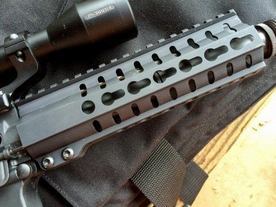 KeyMod attachment points are at the 3, 6, and 9 o'clock positions. The Picatinny rail covers the receiver and hand guard.