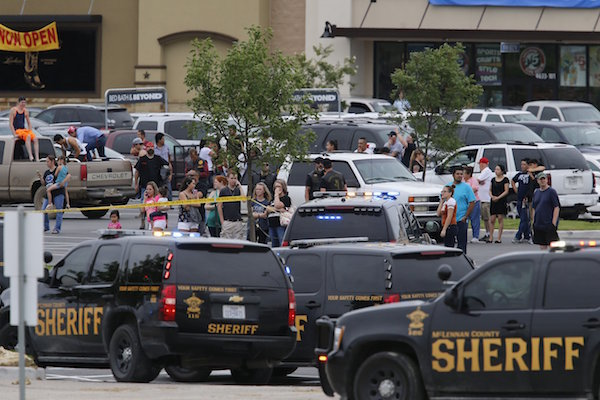 """People at the Central Texas MarketPlace watch a crime scene near the parking lot of a Twin Peaks restaurant Sunday, May 17, 2015, in Waco, Texas. Waco Police Sgt. W. Patrick Swanton told KWTX-TV there were """"multiple victims"""" after gunfire erupted between rival biker gangs at the restaurant. (Rod Aydelotte/Waco Tribune-Herald via AP)"""