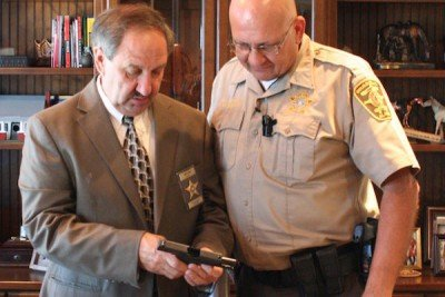 """DeKalb County Sheriff Jimmy Harris inspects the new shipment of concealed carry handguns for his deputies.""  (Photo: YellowHammer News)"