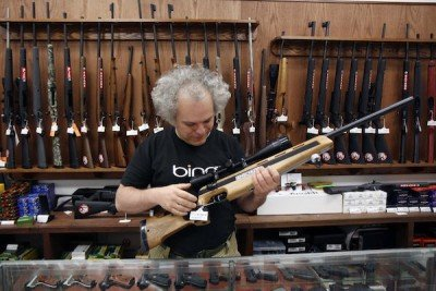 Sergey Solyanik, a software developer for Microsoft and owner of gun retailer Precise Shooter, holds a Anschutz sporting rifle, one of the several firearms for sale at the store, in Green Lake, Thursday, July 9, 2015. Solyanik is concerned that if the gun tax proposed by Seattle City Council President Tim Burgess is approved, he would have to close his doors to business.