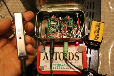 "The classic QRP radio in the Ham world is built into an Altoids tin. Out of curiosity I bought this one on Ebay because it came with a mini antenna tuner, and inside I found the ""other"" Pixie board on Ebay, the one that doesn't have the 5.5mm jack installed in it. This guy taped together two Altoids tins so he'd have room for the battery, and for some reason put an RCA plug for the antenna. But it works! The keyer in my hand is the Te-Ne-Ke portable iambic keyer linked above. This Pixie doesn't support the stereo cord dit/dah either."
