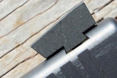 The front edge of the rear sight has a forward slant.