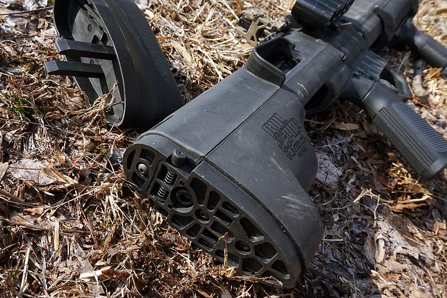 The rear end of the shotgun is secured just behind the thick buttstock.