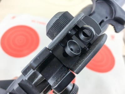 The rear sight includes both large and small apertures for speed and precision respectively.
