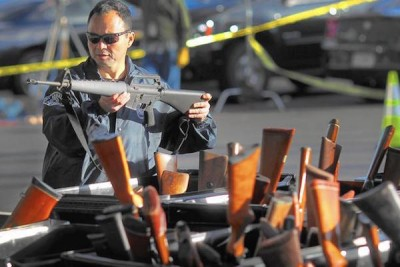 A man looks at a weapon at a gun buyback event at the Los Angeles Memorial Sports Arena in December 2012. Police officials say buybacks help drive down gun-related violence, but some experts question how effective these programs are. (Rick Loomis / Los Angeles Times)