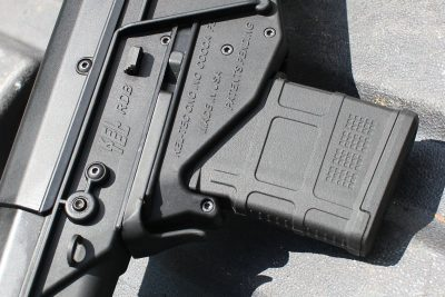 The mag release is a piece of spring steel that wraps around the mag.