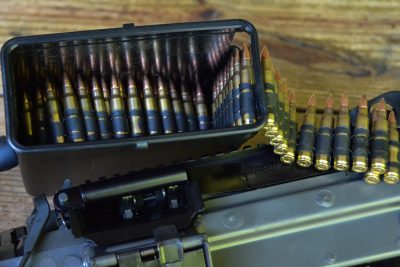The belt of ammunition is held inside a plastic box that is located under the gun.