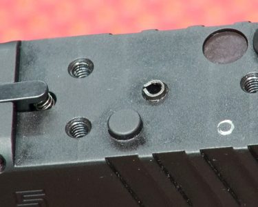 The cover plate protects fine machine threads and the somewhat delicate spring of the loaded chamber indicator.