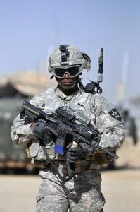 A U.S. Soldier conducts a walk-and-talk through a market in Nassir Wa Salaam, Iraq. He is carrying an M4 Carbine. Image courtesy of DoD.