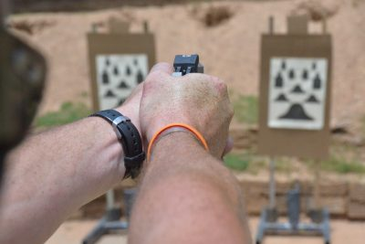 Two-handed shooting. Note how the cocked hammer rests in the web of the hand without pinching.