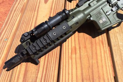 """The short 8.5"""" barrel features an open-pronged muzzle device and is surrounded by a compact handguard."""
