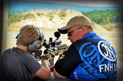 FN USA's Tabor Bright, working with a junior shooter at a side match event. Side matches are events incorporated into competitions, designed to both showcase guns and introduce new shooters in a friendly, one-on-one environment.