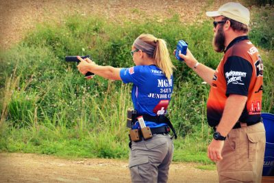 Dean DeTurk, instructing at the MGM Junior camp while Katie Francis shoots pistol.