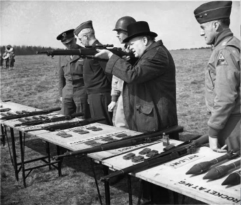 Prime Minister Winston Churchill was always interested in small arms. He is shown here with General Eisenhower inspecting and shooting a selection of infantry weapons, including the new Model 1903A4. Note the ammunition clips on the table. U.S. Army Signal Corps photo.