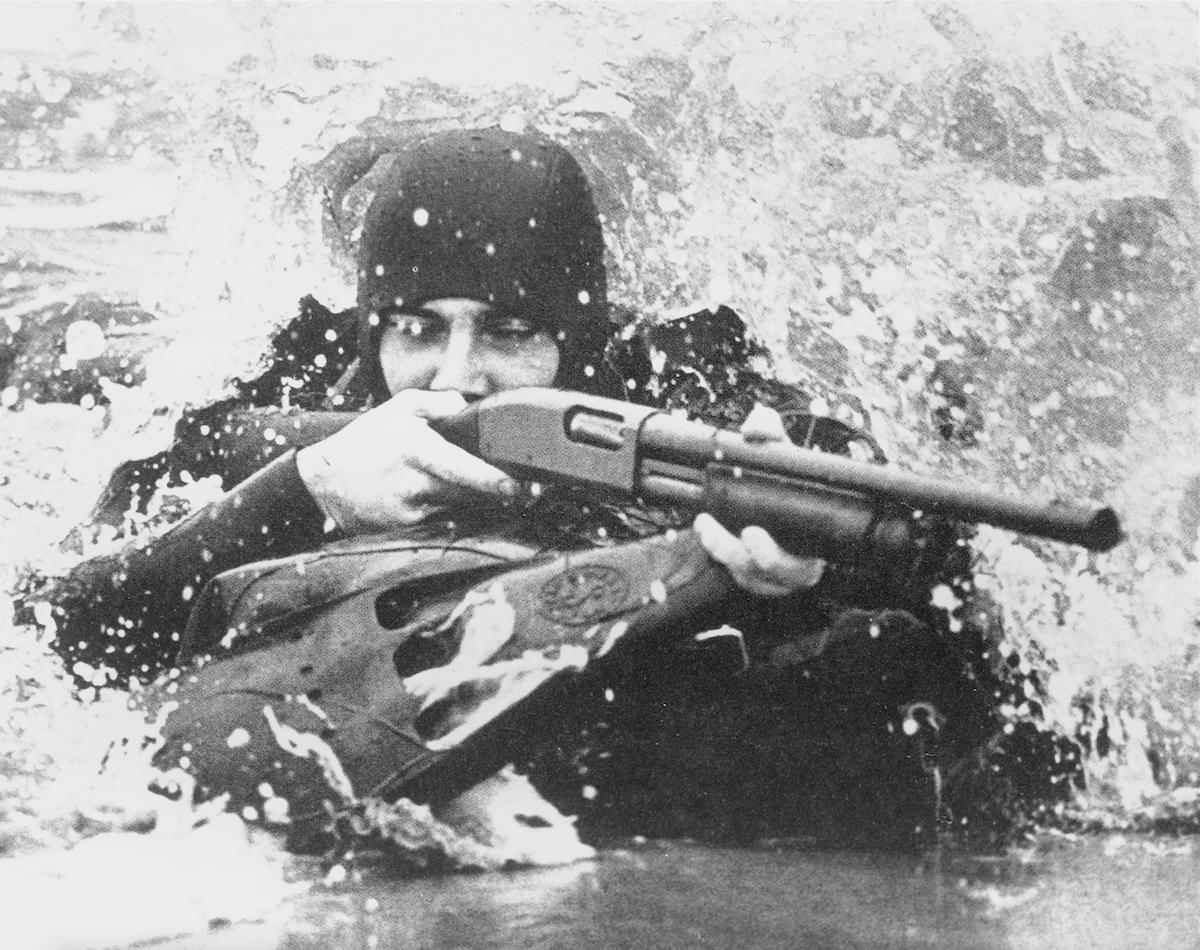 The Remington 870 saw use with the US military in the Vietnam and post-Vietnam eras. An M870 Riot Gun is shown in use here with a U.S. Navy SEAL.