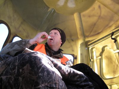 The author survives near blizzard conditions in comfort while enjoying a snack inside a shooting blind during an Iowa deer hunt one December.
