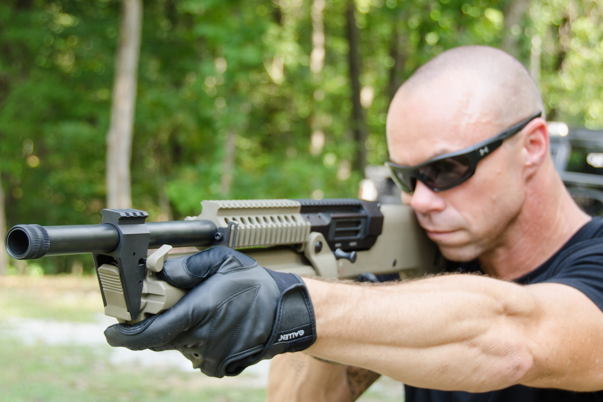 The shooter's support hand is located far forward ready to engage the dual levers (forward of this thumb) that allow the revolving magazine to be rotated.