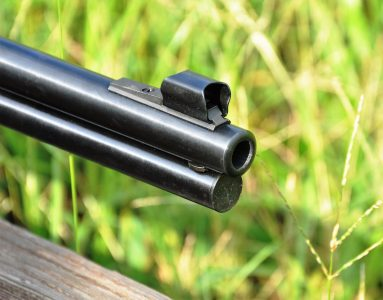 The front sight of the rifle is a hooded ramp sight with a brass bead.