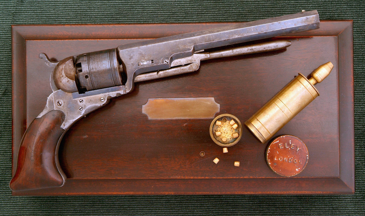 The No. 5 models were later fitted with loading levers which made it possible to reload without taking the gun apart. This cased example also has the later single nozzle power flask since the cylinder did not have to be removed to reload.