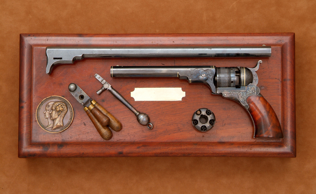 Pictured is an exceptional two barrel cased No. 2 Model. Among options offered with the No. 2 was a 12-inch barrel. A rare presentation, this example has vine scroll engraving, color casehardened frame and hammer, and German silver bands on the barrel and recoil shield. The extra 12-inch barrel was neither engraved nor silver inlayed.